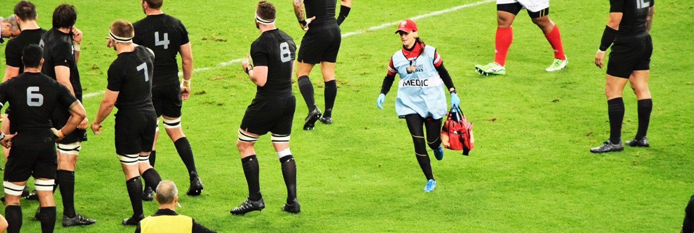 Megan Sturley Physitherapist running on field to tend a Tongan rugby player during the Rugby World Cup